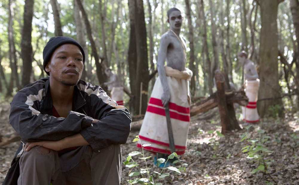 Film still from The Wound (2017):  Protagonist squats in forest with figures in background
