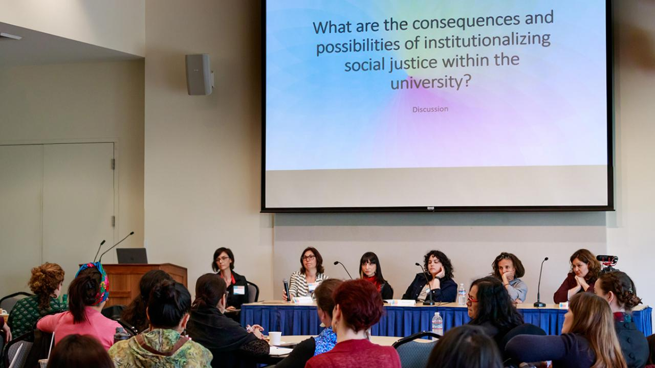 "Photo: audience view of panelists beneath slide that reads, ""What are the consequences and possibilities of institutionalizing social justice within the university?"""