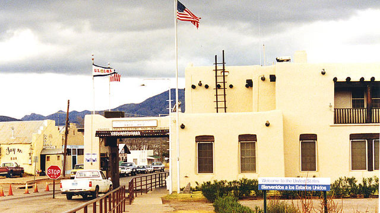 Border station at Naco, Texas. White adobe structure with U.S. flag flying overhead