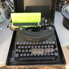 Black typewriter with green paper